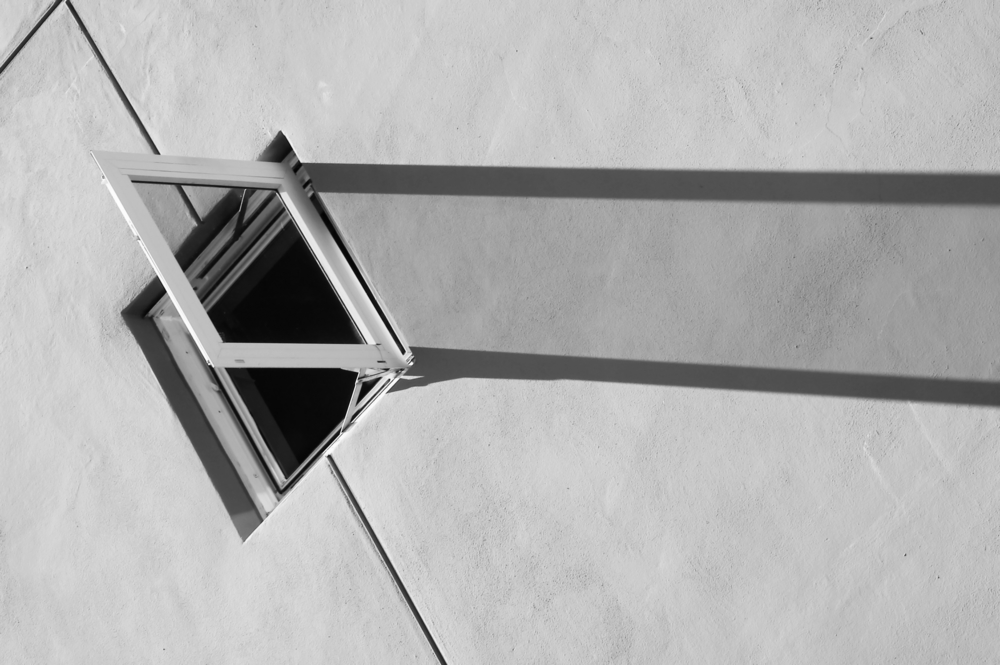 Open window and its long shadow on a sunlit wall