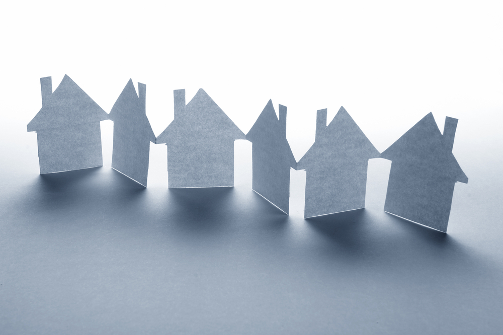 close up of houses cut out of paper on white background
